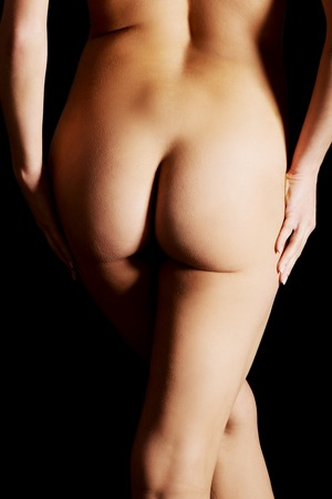 naked woman  white background: Beautiful woman buttocks over dark background.
