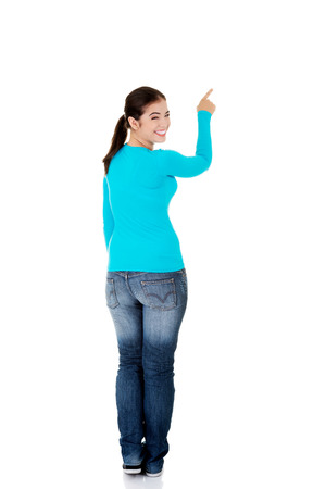 standing: Back view of a woman pointing up.