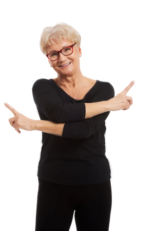 on both sides: Happy senior woman pointing on both sides Stock Photo