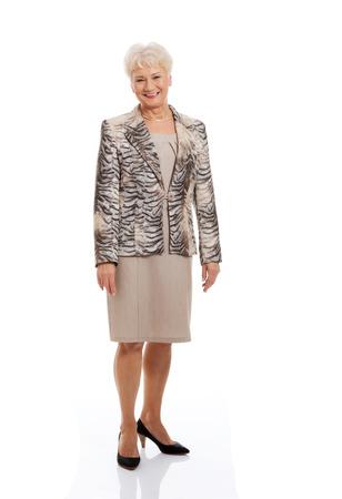one senior adult woman: Friendly fashionable senior woman standing