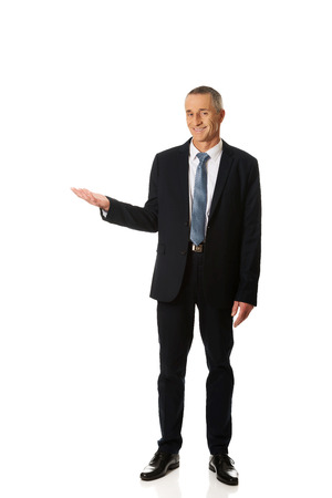 Full length smiling businessman holding copyspace. photo