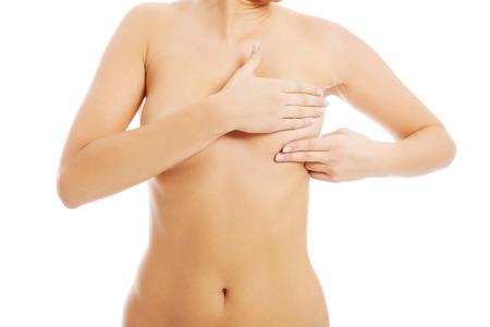 topless: Jeune femme aux seins nus fait l'auto-examen des seins. Sur fond blanc.