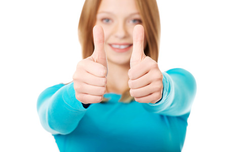 both: Happy teenager showing thumbs up with both hands