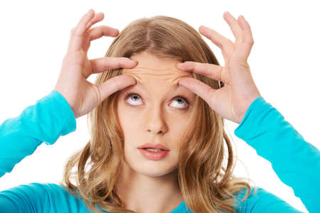 Teenage woman checking wrinkles on forehead