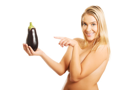 aubergine: Nude woman showing an aubergine by a finger. Stock Photo