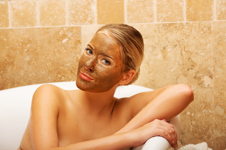 chocolate mask: Relaxed spa woman sitting in a bath with face mask