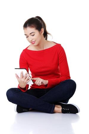 crosslegged: Student woman sitting cross-legged using a tablet.