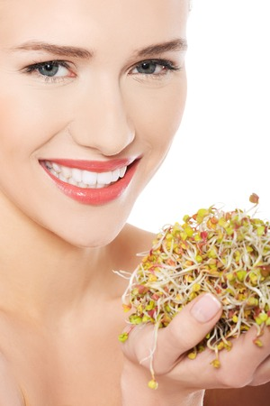 Close up nude woman holding sunflower sprouts. photo