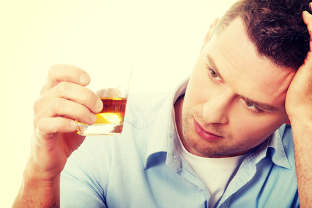 alcohol abuse: Yound man in depression, drinking whisky