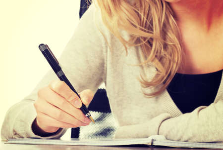 escribiendo: De escritura a mano, mano escribe con una pluma en un cuaderno