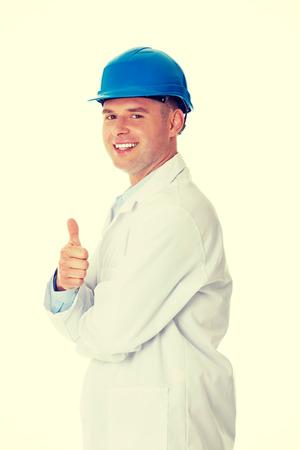 bata de laboratorio: Hombre en una bata de laboratorio y un casco, ingeniero, maestro o qu�mica que gesticula OK Foto de archivo