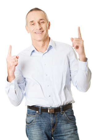 man pointing up: Happy mature man pointing up.