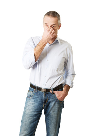 sinus: Mature man holding his nose because of a sinus pain. Stock Photo