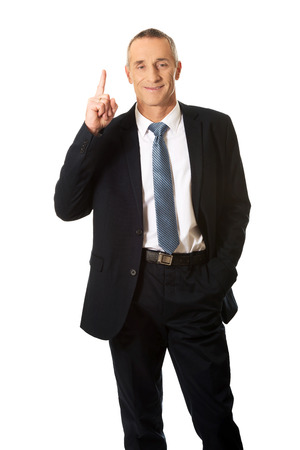 one hand: Businessman pointing upwards with one hand.