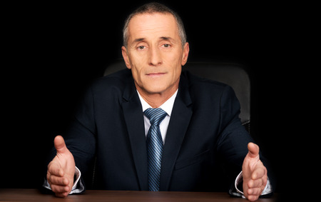 open shirt: Serious businessman sitting at desk with open hands. Stock Photo