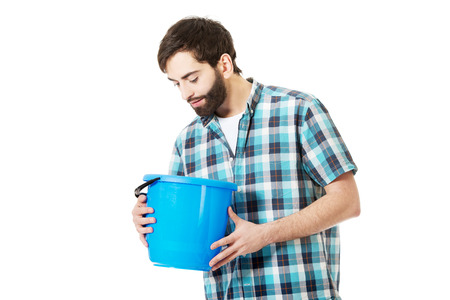 looking into: Young handsome man looking into plastic blue bucket.