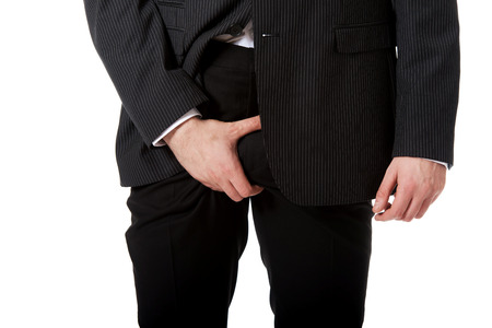 crotch: Young businessman holding his crotch because of pain. Stock Photo
