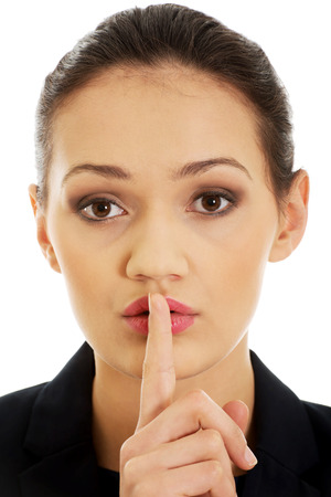 Businesswoman making silent sign with finger on lips. photo