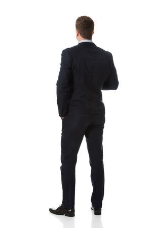 Handsome businessman standing back to camera.