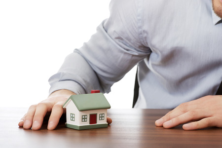 Happy businessman with house model by a desk. photo