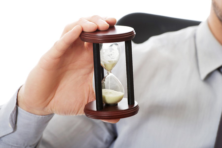 rushing hour: Businessman holding hourglass in the office.