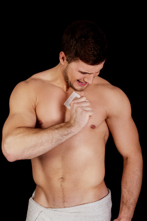 depilation: Handsome muscular man waxing his chest.