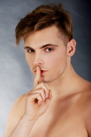 topless: Young handsome man with finger on lips.