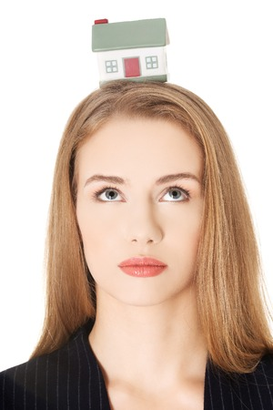 Beautiful woman holding a house model on head photo
