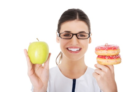 Happy nutritionist holding a cake and apple