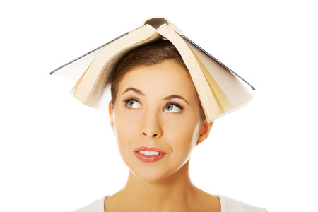 happy teenager: Woman smiling holding book on head Stock Photo