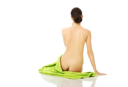 mujer desnuda sentada: Vista trasera de la mujer desnuda sentada en una toalla.