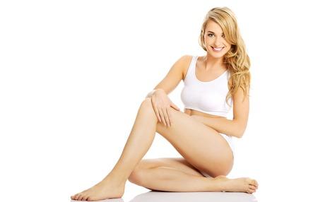 Junge Frau in Unterwäsche sitzen auf dem Boden