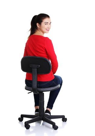 mujer sentada: Mujer feliz joven que se sienta en una silla Foto de archivo