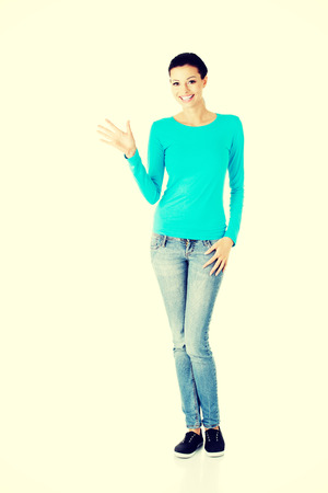 Beautiful smiling woman showing welcome gesture. photo