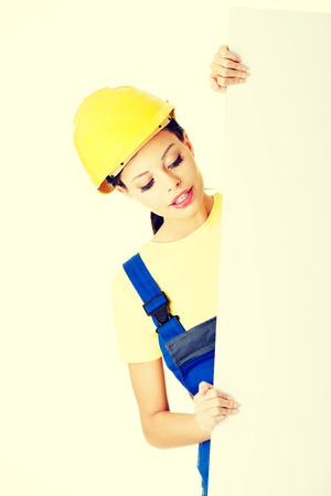 Happy female constructor holding empty banner. photo