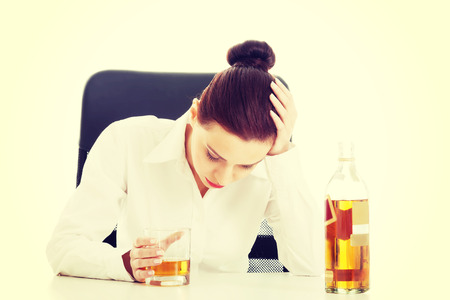 Depressed businesswoman in depression drinking alcohol. photo