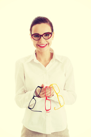 Beautiful young woman holding three pair of glasses. photo