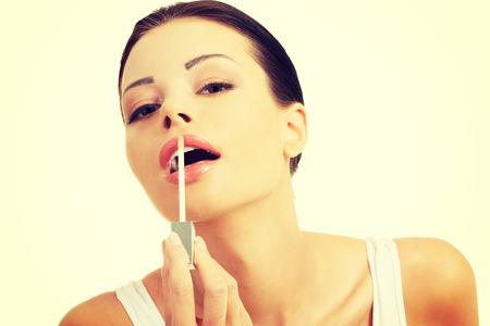 lipgloss: Beautiful young caucasian woman applying lipgloss. Stock Photo