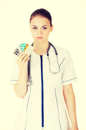 doctor holding pills: Beautiful female doctor holding pills.