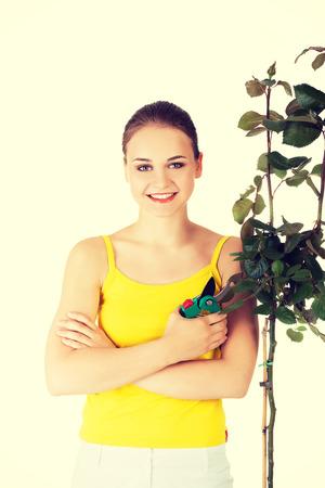 Happy gardener woman using pruning scissors. photo