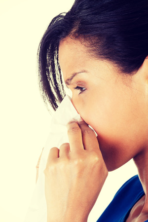 bedridden: Woman sneezing in a tissue.