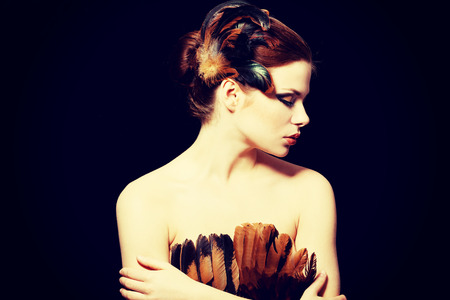 Beautiful woman with brown professional make-up with feathers.