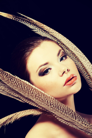 eyeshades: Beautiful woman with brown professional make-up with feathers.