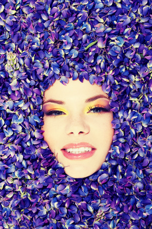 eyeshades: Beutiful young woman with colorful makeup and violet flowers of lupin.