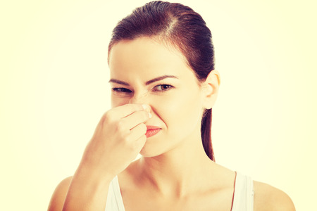 bad smell: Woman pinches her nose to block a bad smell.
