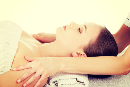 massaged: Woman lying on a massage table and is being massaged. Stock Photo
