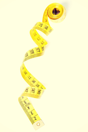 enrolled: One enrolled yellow measuring tape. Stock Photo
