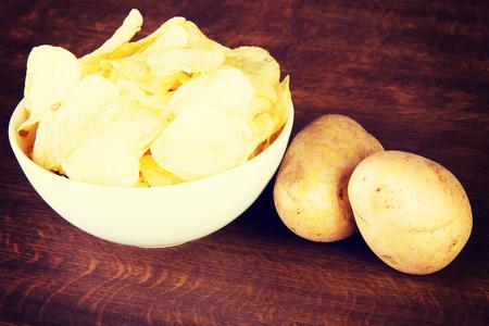 potatoe: Potatoe chips in a bowl and potatoes on a table. Stock Photo