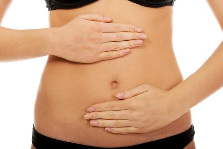 vientre femenino: Mujer joven que toca su vientre. Foto de archivo