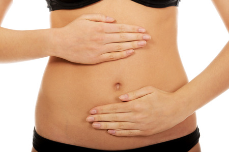 human stomach: Young woman touching her belly. Stock Photo
